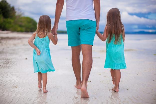 熱帯の白いビーチで家族の背面図