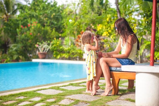 若い母親と彼女の小さな娘は、スイミングプールのそばで楽しい時を過す