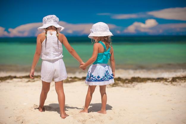 白い熱帯のビーチで海を見ている妹