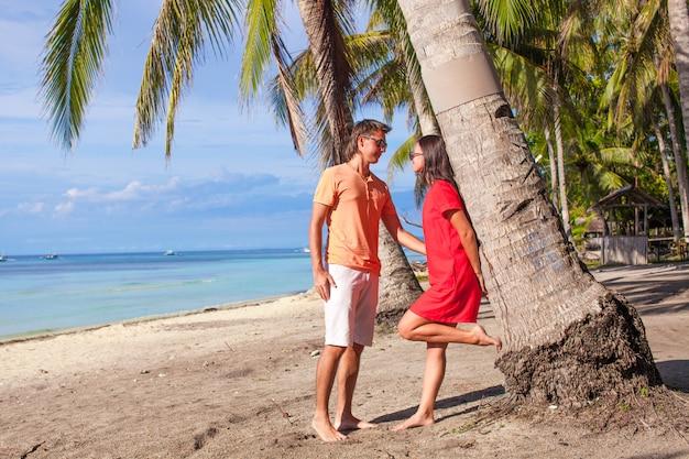 ヤシの木の近くの熱帯のビーチでロマンチックなカップル