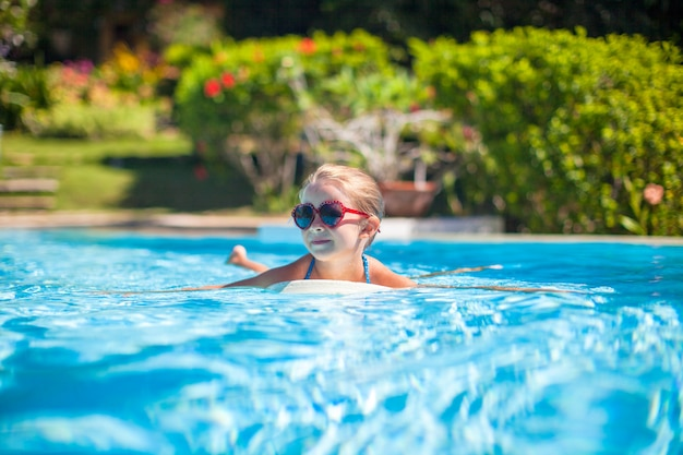 愛らしい幸せな少女は、スイミングプールで泳ぐ