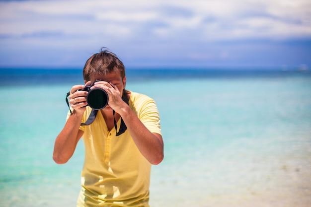 若い男が熱帯のビーチで彼の手でカメラで撮影