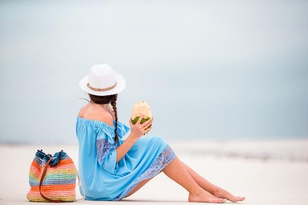 熱帯の休暇中にココナッツミルクを飲む若い女性