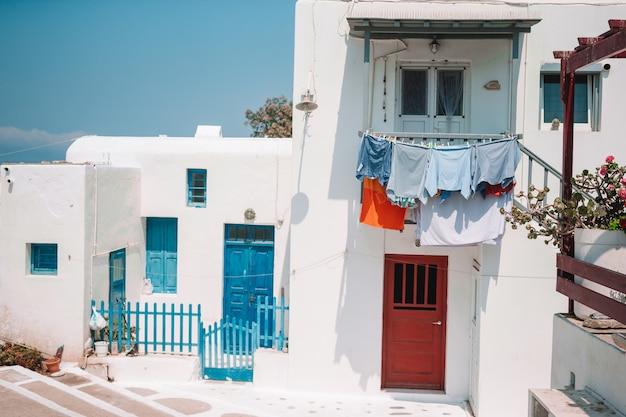青いバルコニー、階段、花のある島の狭い通り。