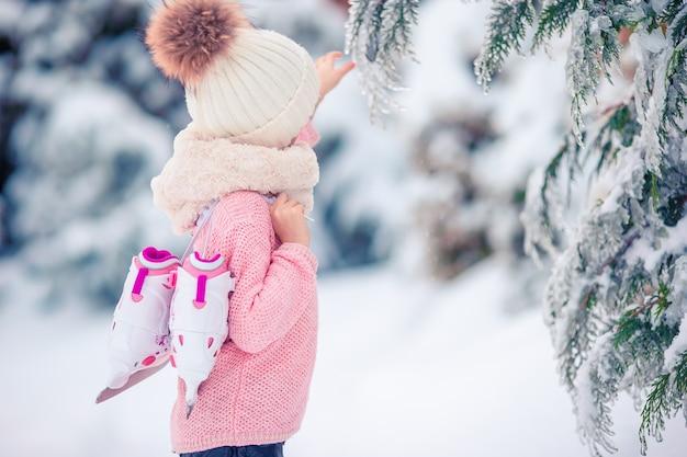 かわいい小さな子供の女の子は屋外でスケートをします。