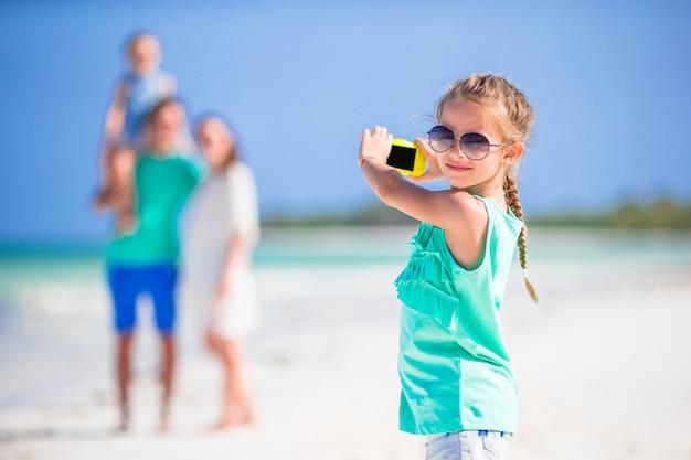 小さな女の子がビーチで家族の電話で写真を作る