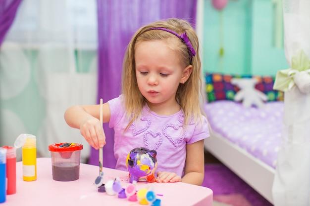 小さな女の子は部屋の彼女の机で塗料を描画します
