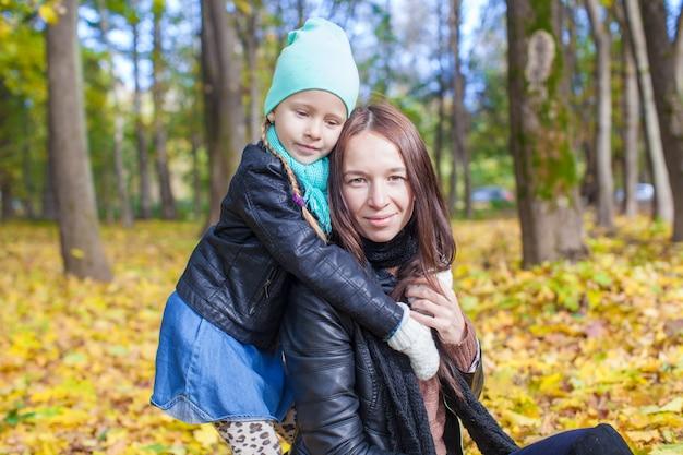 幸せな母と暖かい晴れた日に黄色の秋の森で楽しんでいるかわいい娘