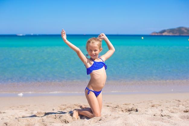 熱帯白い砂浜でホイールを作る愛らしい少女