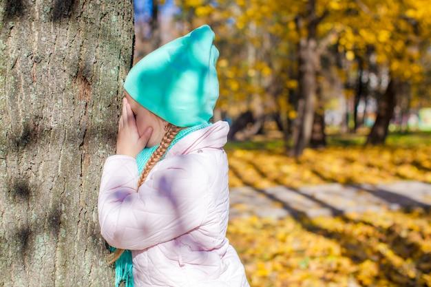 Маленькая девочка играет в прятки возле дерева в осеннем парке