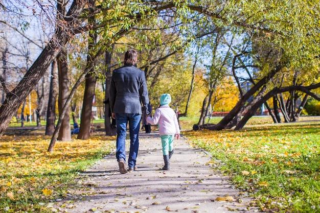 若い父親と秋の公園を歩く少女の背面図