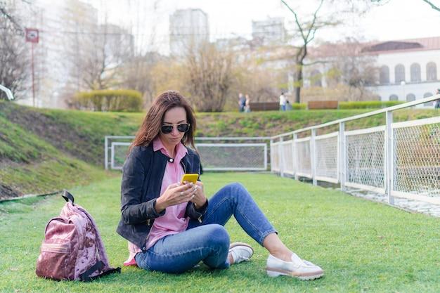 路上で屋外の携帯電話を持つ女性。女性が携帯のスマートフォンを使用しています。