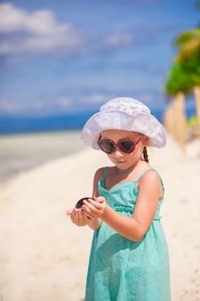 Очаровательная маленькая девочка на тропическом пляже в филиппинах с раковиной в руке