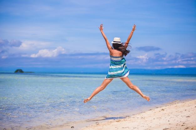 ジャンプしてビーチで腕を上げる若い女性