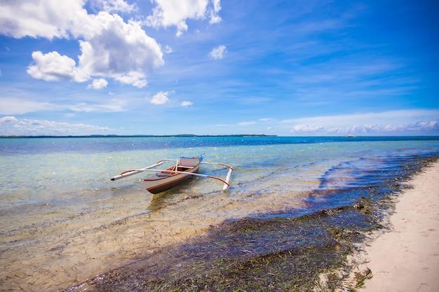 白い熱帯のビーチで小さな漁船