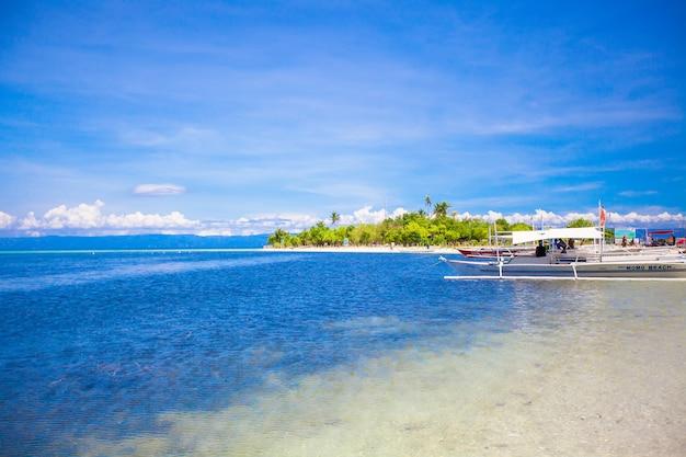 白い熱帯のビーチで小さなボート