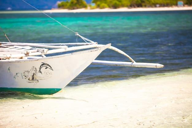 白い砂浜の熱帯のビーチで小さなボート