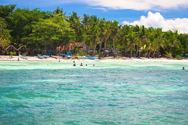 緑のヤシの木、白い砂浜、青緑色の水と完璧なビーチのパノラマビュー