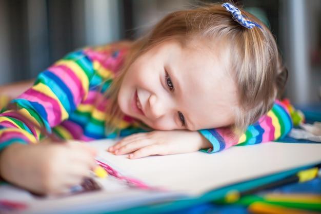 彼女のテーブルに座って鉛筆で絵かわいい女の子