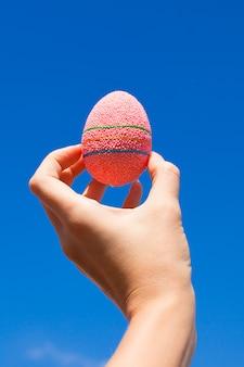 手に明るい美しいピンクのイースターエッグ