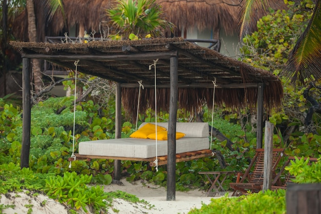 熱帯のエキゾチックな白いプラージュの木の間のビーチベッド