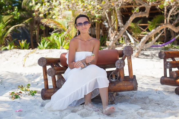 エキゾチックなトロピカルリゾートの木の椅子に座っている若いセクシーな女性