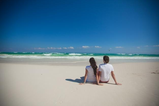 熱帯の白いビーチに座っている若いカップルの背面図