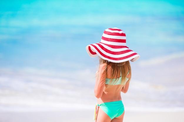 カリブ海の白い砂浜に沿って歩いて大きな赤い帽子の愛らしい少女