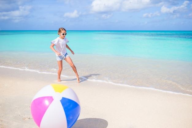 Очаровательная маленькая девочка играет с мячом на пляже, детский летний спорт на открытом воздухе