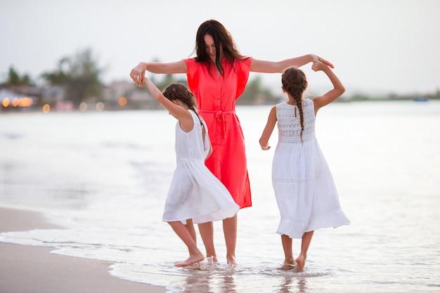 Красивая мама и ее очаровательные маленькие дочери на пляже