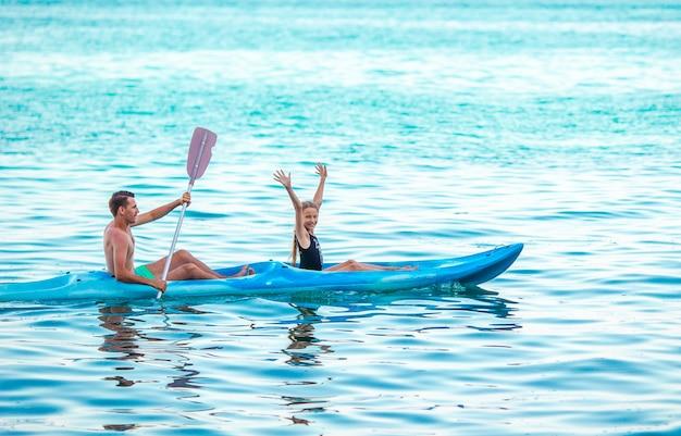 一緒に海でカヤックをするスポーティな魅力的な家族