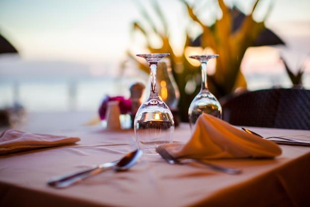 夕暮れ時のセットテーブルにクローズアップの空のワイングラス