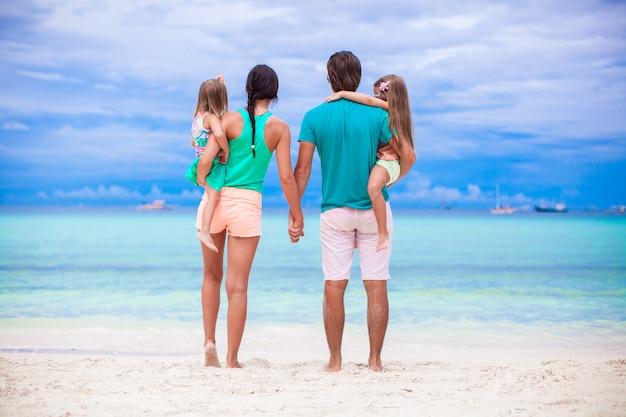 フィリピンの海を見ている若い家族の背面図