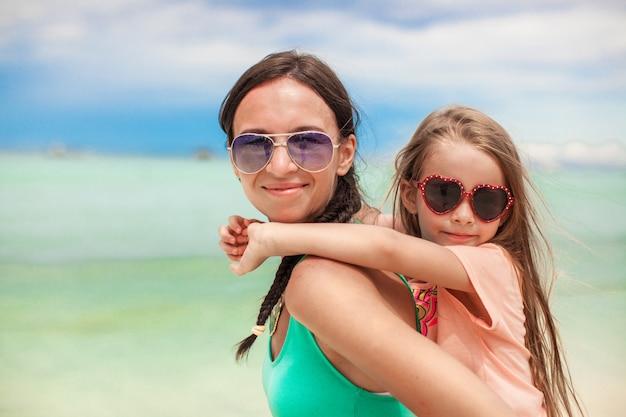 若い母親と彼女の小さな娘がビーチでの休暇を楽しんで