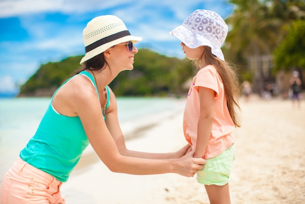 クローズアップの少女は、ビーチで彼女の若い母親を保持しています。