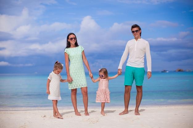 Модная семья из четырех человек гуляет по морю и наслаждается пляжным отдыхом