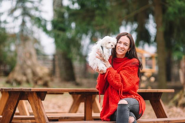 白い子犬を持つ女性。美しい少女の手の中の子犬