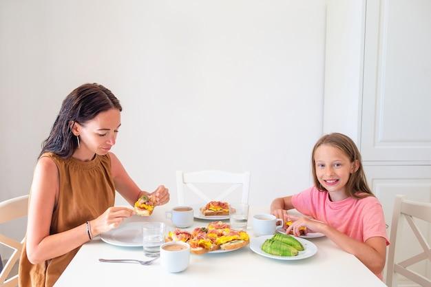 キッチンで一緒に朝食を食べて幸せな家族