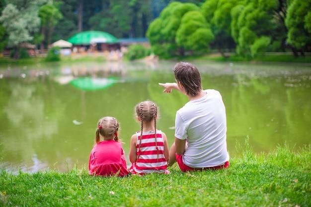 幸せな父と小さな娘たちは湖でリラックスします。