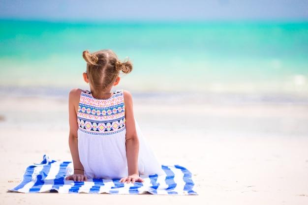愛らしい少女は、休暇中に熱帯のビーチで楽しい時を過す