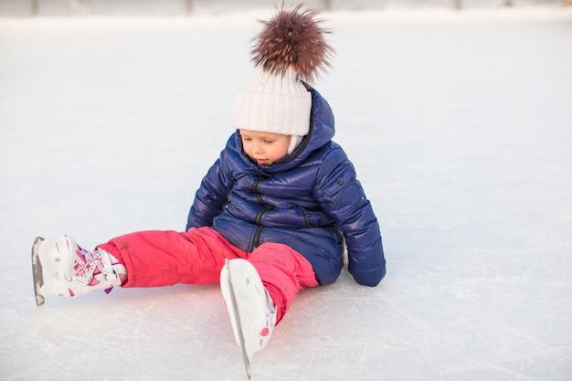 落下後スケートで氷の上に座っている愛らしい少女