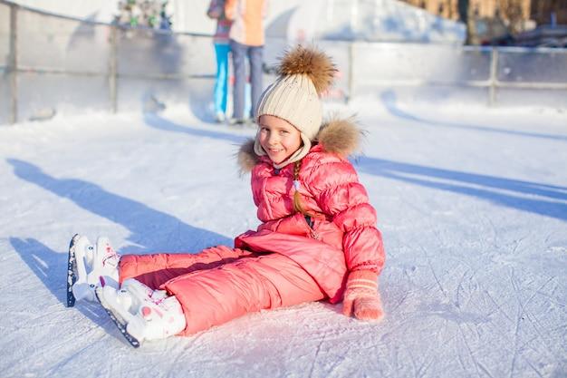 Счастливая прелестная девушка сидя на льде с коньками после падения