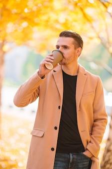 秋の公園屋外で携帯電話でコーヒーを飲む若い男