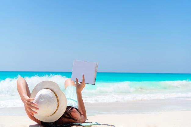 海岸で本を持つ女性
