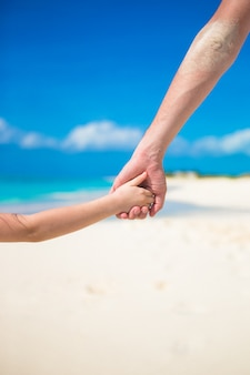 父とビーチでお互いに手を繋いでいる小さな娘のクローズアップ