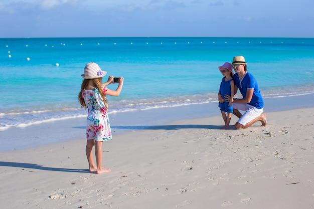 ビーチで彼女の家族の電話で写真を作る少女