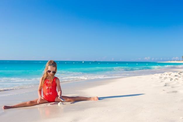 白い砂浜で分割の上に座っている小さな女の子
