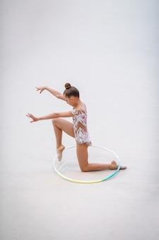 Маленькая гимнастка тренируется на ковре и готова к соревнованиям