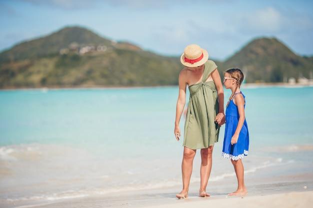 夏休みを楽しんでいるカリブ海のビーチで美しい母と娘。