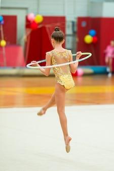 カーペットの上の彼女のパフォーマンスを持つ美しい小さなアクティブな体操の女の子